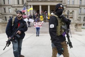 ASSOCIATED PRESS                                 Protesters carry rifles near the steps of the Michigan State Capitol building in Lansing, Mich., today. Flag-waving, honking protesters drove past the Michigan Capitol to show their displeasure with Gov. Gretchen Whitmer's orders to keep people at home and businesses locked during the coronavirus outbreak.