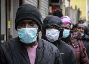 ASSOCIATED PRESS                                 People wait for a distribution of masks and food from the Rev. Al Sharpton in the Harlem neighborhood of New York.