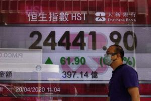 ASSOCIATED PRESS                                 A man wearing face mask walks past a bank electronic board showing the Hong Kong share index at Hong Kong Stock Exchange today. Shares were mixed in Asia, while oil prices have fallen back.