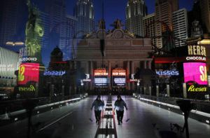 ASSOCIATED PRESS                                 A lone worker wearing a mask cleans a pedestrian walkway devoid of the usual crowds as casinos and other business are shuttered due to the coronavirus outbreak in Las Vegas on April 18. Nevada's governor closed the glitzy casinos and nightlife attractions in mid-March, leaving much of the famous gambling mecca empty, barricaded and abandoned.