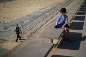 ASSOCIATED PRESS                                 A child looks as a police officer patrols the promenade of the beach, where access is prohibited, in Barcelona, Spain.