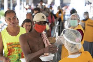 ASSOCIATED PRESS                                 Volunteers from a Christian church serve food to homeless people during a quarantine imposed by the state government to help contain the spread of the new coronavirus in Sao Paulo, Brazil, today.