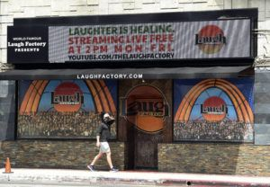 """ASSOCIATED PRESS                                 A pedestrian walked underneath a marquee advertising a """"Laughter is Healing"""" stand-up comedy livestream event at the Laugh Factory in Los Angeles last Monday."""