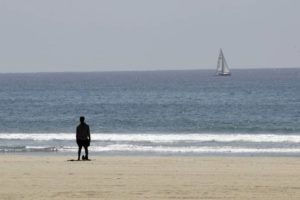 ASSOCIATED PRESS                                 A lone visitor looks out onto the Pacific ocean at the closed-off Venice Beach in Los Angeles.