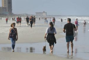 WILL DICKEY/THE FLORIDA TIMES-UNION VIA AP                                 Beachgoers celebrated the beaches opening on a limited basis during the coronavirus pandemic on Jacksonville Beach, Florida. The beaches are open from 6 a.m. to 11 a.m. and then 5 p.m. to 8 p.m. for activities such as walking, running, surfing, swimming, fishing and other activities. No sunbathing or sitting is allowed.
