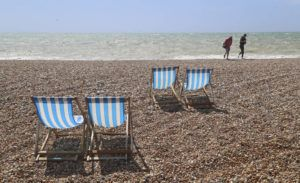 GARETH FULLER/PA VIA AP People walk on a near empty beach as the hot weather cools following scenes of people flocking to parks and beaches after lockdown measures to curb the spread of coronavirus were eased, in Brighton, England.