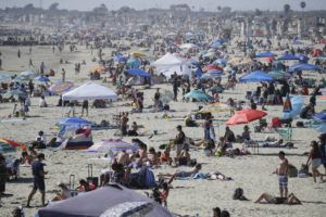 ASSOCIATED PRESS                                 Visitors gather on the beach in Newport Beach, Calif.