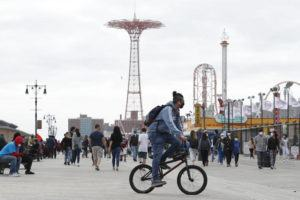 ASSOCIATED PRESS A young man wearing a protective face mask rides his bicycle along a fairly crowded Coney Island boardwalk during the current coronavirus outbreak on Sunday in New York. No swimming was allowed and social distancing reminders were abundant on the beach as Memorial Day weekend kicked off the first weekend of summer.