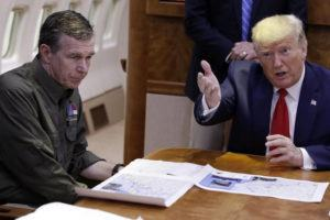 """ASSOCIATED PRESS President Donald Trump participates in a briefing about Hurricane Dorian with North Carolina Gov. Roy Cooper, left, aboard Air Force One at Marine Corps Air Station Cherry Point in Havelock, N.C., in September 2019. President Donald Trump demanded today that North Carolina's Democratic governor sign off """"immediately"""" on allowing the Republican National Convention to move forward in August with full attendance despite the ongoing COVID-19 pandemic. Trump's tweets today about the RNC, planned for Charlotte, come just two days after the North Carolina recorded its largest daily increase in positive cases yet."""