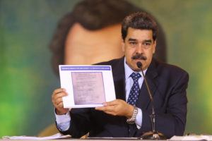 ASSOCIATED PRESS                                 In this photo released by the Venezuela's Miraflores presidential press office, President Nicolas Maduro accused opposition leader Juan Guaido of being behind a military raid designed to oust him, as he holds a copy of a written agreement that allegedly bears Guaido's signature as evidence.