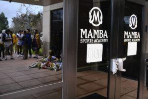 ASSOCIATED PRESS Los Angeles Lakers fans and a memorial are reflected in the window of the Mamba Sports Academy in Thousand Oaks, Calif., on Jan. 26, following reports of NBA star Kobe Bryant's death in a helicopter crash in southern California.
