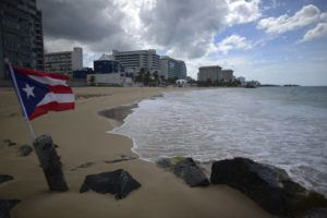 ASSOCIATED PRESS                                 A Puerto Rican flag flies on an empty beach at Ocean Park, in San Juan, Puerto Rico.