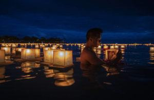 STAR-ADVERTISER / 2019                                 Edward Palma cradled a lantern dedicated to his mother, Estarlina Penalba, at the Shinnyo Lantern Floating Hawaii 2019 Ceremony held at Ala Moana Regional Park on Memorial Day. Approximately 50,000 people gathered to set 7,000 lanterns afloat in remembrance of loved ones.