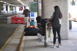 BRUCE ASATO / BASATO@STARADVERTISER.COM                                 Travelers wait curbside for pickup at Daniel K. Inouye International Airport on April 30.