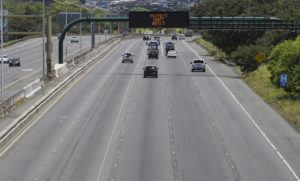 """STAR-ADVERTISER / April 26                                 A message board on H-1 Freeway near Joint Base Pearl Harbor-Hickam alternately displays """"STAY HOME"""" and """"PROTECT DON'T INFECT"""" messages to motorists on April 26."""