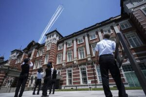 ASSOCIATED PRESS                                 Station staff look at Blue Impulse of the Japan Air Self-Defense Force flying over the Tokyo Station to show support towards medical staff battling the COVID-19 pandemic, May 29, in Tokyo.