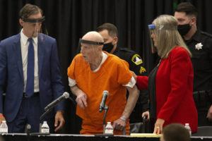 ASSOCIATED PRESS / JUNE 29 Joseph James DeAngelo, center, charged with being the Golden State Killer, is helped up by his attorney, Diane Howard, as Sacramento Superior Court Judge Michael Bowman enters the courtroom in Sacramento, Calif. DeAngelo pleaded guilty to multiple counts of murder and other charges 40 years after a sadistic series of assaults and slayings in California. Due to the large numbers of people attending, the hearing was held at a ballroom at California State University, Sacramento to allow for social distancing.