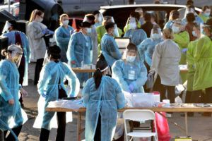 ASSOCIATED PRESS Medical personnel prepared to test hundreds of people lined up in vehicles in Phoenix's western neighborhood of Maryvale for free COVID-19 tests on Sunday.