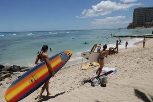 JAMM AQUINO / JAQUINO@STARADVERTISER.COM                                 Surfers carry their boards on Friday in Waikiki. With Hawaii's low coronavirus infection rate, many residents have taken to resuming outdoor activities. However, Waikiki remains nearly devoid of tourists who power the state's economy.
