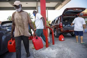 AP                                 A resident walks with containers filled with gasoline at Cooper's gas station before the arrival of Hurricane Isaias in Freeport, Grand Bahama, Bahamas.