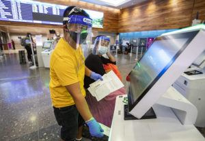 CINDY ELLEN RUSSELL / CRUSSELL@STARADVERTISER.COM                                 Interisland travelers Dhen Agustin and Mary Jane Gaspar check-in for an flight at the Hawaiian Airlines kiosk at Daniel K. Inouye International Airport. Travelers from Oahu still must quarantine for 14 days when they visit a neighbor island.