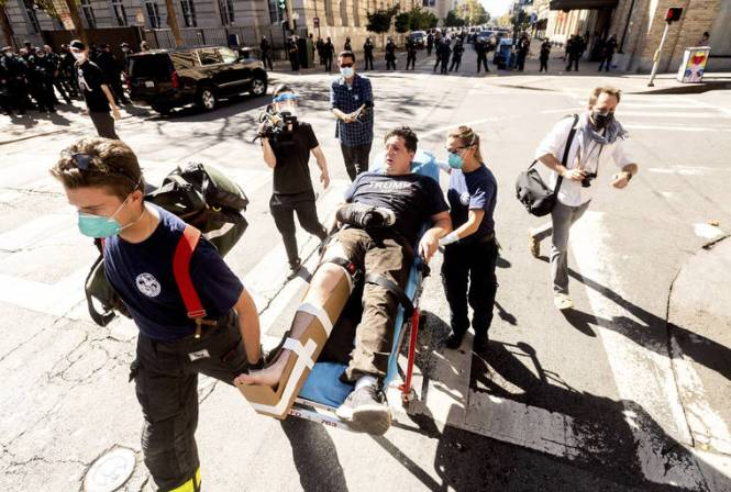NOAH BERGER / ASSOCIATED PRESS                                 Medics transport a supporter of President Donald Trump to an ambulance after he was attacked by counter-protesters in San Francisco today.