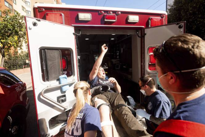 NOAH BERGER / ASSOCIATED PRESS                                 Medics transport a supporter of President Donald Trump to an ambulance after he was attacked by counter-protesters in San Francisco today. About a dozen pro-Trump demonstrators were met by several hundred counter-protesters as they tried to rally.