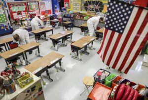 ASSOCIATED PRESS                                 Custodial workers clean a classroom at Richard A. Simpson Elementary School in Arnold, Mo., on Nov. 5. The school went to fully virtual learning on Nov. 2 after more than 5% of the staff and students tested positive for COVID-19.
