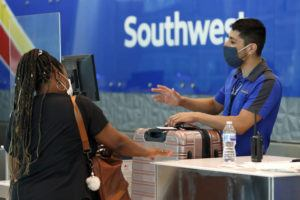 ASSOCIATED PRESS                                 Southwest Airlines employee Oscar Gonzalez, right, assists a passenger at the ticket counter at Love Field in Dallas in June.
