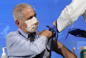 ASSOCIATED PRESS                                 Dr. Anthony Fauci, director of the National Institute of Allergy and Infectious Diseases, prepares to receive his first dose of the COVID-19 vaccine at the National Institutes of Health in Bethesda, Md., on Tuesday.