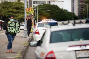 CINDY ELLEN RUSSELL / CRUSSELL@STARADVERTISER.COM                                 Above, Aileen Witt held a sign along Beretania Street at the state Capitol on Wednesday in support of local farmers.