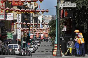 ASSOCIATED PRESS                                 A masked worker cleans a street in the Chinatown district in San Francisco.