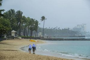 DENNIS ODA / 2020                                 Beachgoers in Waikiki cover themselves up for protection from the heavy downpour.