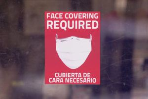 ASSOCIATED PRESS                                 A mask required sign is displayed on the entrance to a business in Dallas.
