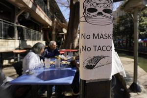 ASSOCIATED PRESS A sign requiring masks is seen near diners eating at a restaurant on the River Walk, Wednesday, in San Antonio.
