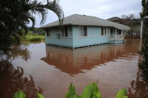 JAMM AQUINO / JAQUINO@STARADVERTISER.COM                                 A house on Haleiwa Road is surrounded by floodwaters Tuesday in Haleiwa.