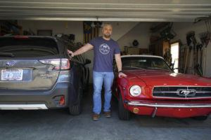ASSOCIATED PRESS / MARCH 5                                 Steve Bock stands between his new Subaru Outback and his 1965 Ford Mustang at his home in Apex, N.C.