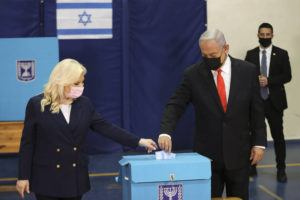 RONEN ZVULUN/POOL VIA ASSOCIATED PRESS                                 Israeli Prime Minister Benjamin Netanyahu and his wife Sara cast their ballots at a polling station as Israelis voted in a general election, in Jerusalem, today. The exit polls on Israel's three main TV stations indicated that both Netanyahu and his religious and nationalist allies, along with an anti-Netanyahu group of parties, both fell short of the parliamentary majority required to form a new government.