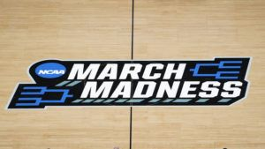 ASSOCIATED PRESS                                 The March Madness logo was shown on the court during the first half of a men's college basketball game in the first round of the NCAA tournament at Bankers Life Fieldhouse in Indianapolis. A Supreme Court case being argued this week amid March Madness could erode the difference between elite college athletes and professional sports stars.