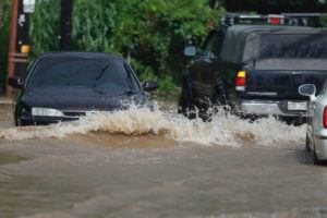 JAMM AQUINO / JAQUINO@STARADVERTISER.COM                                 Vehicles navigate flood water along Kamehameha Highway near Kahaluu.