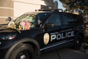 NEW YORK TIMES                                 Flowers on a police vehicle become a makeshift memorial outside the Boulder Police Department in Boulder, Colo., Tuesday, to slain Boulder Police Officer Eric Talley, 51, who was killed in a mass shooting at a grocery store a day earlier.