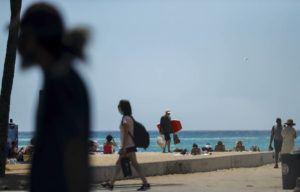 JAMM AQUINO / APRIL 5                                 Honolulu remains under Tier 3 coronavirus pandemic restrictions despite a recent rise in infection cases in the state. Shown here, beachgoers, some with and others without masks, are seen near the Kapahulu Groin in Waikiki.