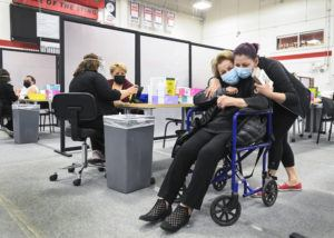 ASSOCIATED PRESS                                 Manda Zand, right, hugs her grandmother Farang Ahmadkorour, 92, after she received her COVID-19 vaccine at the Seneca College mass vaccination site during the coronavirus pandemic in Toronto, today.