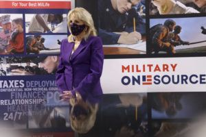 POOL VIA                                 First lady Jill Biden points to a military service member pictured on a sign as she tours Military One Source, an active duty military resource hub/call center for service members, their family and survivors, in Arlington, Va.