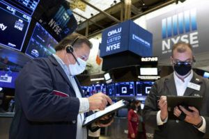 COURTESY NEW YORK STOCK EXCHANGE VIA AP                                 Traders John Santiago, left, and William Lawrence, work on the trading floor today.