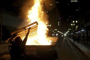DAVE KILLEN/THE OREGONIAN VIA AP                                 Protesters light a fire in a dumpster in downtown Portland, Ore. Police in Portland, said Saturday they arrested several people after declaring a riot Friday night when protesters smashed windows, burglarized businesses and set multiple fires during demonstrations that started after police fatally shot a man while responding to reports of a person with a gun.