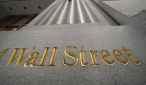 ASSOCIATED PRESS / 2020                                 A sign for Wall Street is carved in the side of a building.