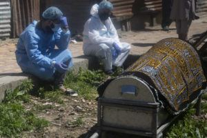 ASSOCIATED PRESS                                 Relatives mourn near a coffin containing the body of a person who died of COVID-19 in Srinagar, Indian controlled Kashmir, today. India's crematoriums and burial grounds are being overwhelmed by the devastating new surge of infections tearing through the populous country with terrifying speed, depleting the supply of life-saving oxygen to critical levels and leaving patients to die while waiting in line to see doctors.