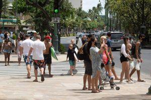 CRAIG T. KOJIMA / CKOJIMA@STARADVERTISER.COM                                 Visitors have been returning to Waikiki in greater numbers in recent weeks. Here, pedestrians crowd a sidewalk in Waikiki on Saturday.