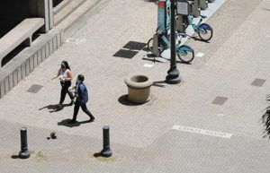 JAMM AQUINO / JAQUINO@STARADVERTISER.COM                                 Two pedestrians with masks walk Fort Street Mall on Monday in Honolulu.